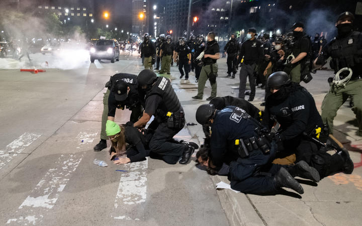 Detroit Police arrest a protester near the Detroit Police station, as protesters march through the streets of Detroit, Michigan for a second night.