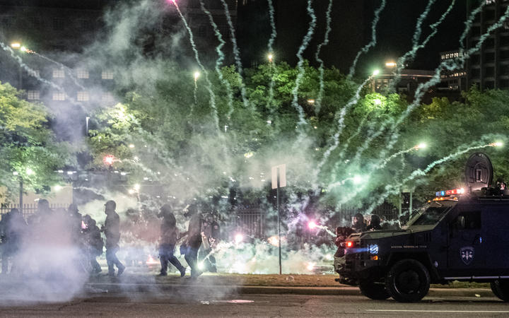 Tear gas canisters explode near some Detroit Police units who attempted to break up protesters, through the streets of Detroit, Michigan for a second night.