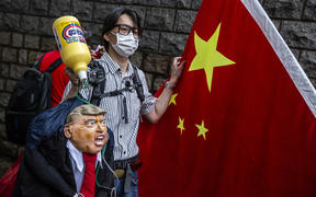 A pro-China activist holds an effigy of US President Donald Trump during a protest outside the US consulate in Hong Kong on May 30, 2020, in response to Trump's sanctions pledge.