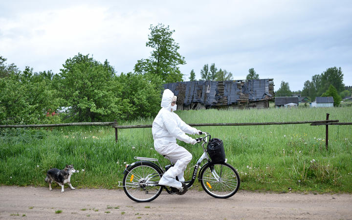 Paramedic Nadezhda Konanava, 65, wearing a protective suit rides her electric bike at the village of Novaya Obo.