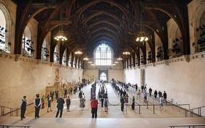 A handout photograph released by the UK Parliament shows members of parliament queuing in Westminster Hall to vote.