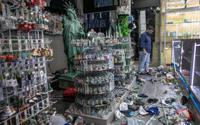 A shop owner looks over damage in a looted souvenir shop near Times Square a