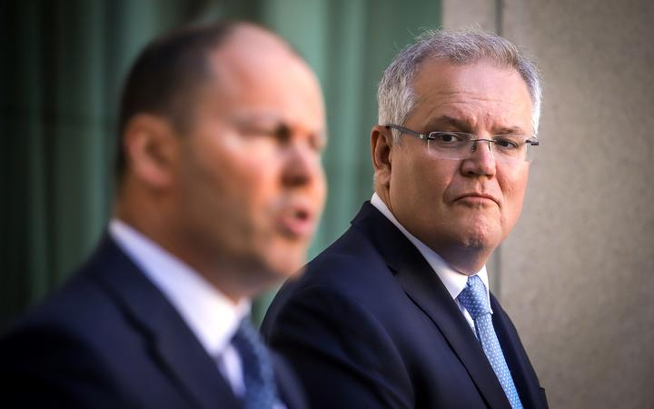 Australian Prime Minister Scott Morrison reacts as he stands with the Australian Treasurer Josh Frydenberg