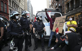 Protesters demand to kneel down from police officers with the call for unity during a protest in New York