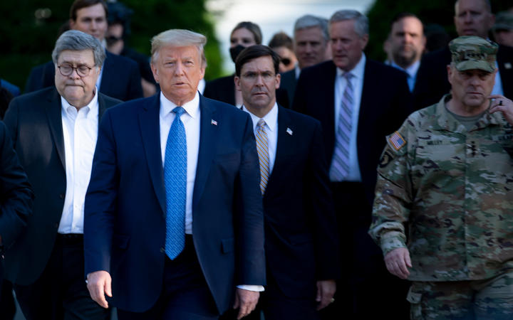 US President Donald Trump walks with Attorney General William Barr, left, Secretary of Defense Mark T. Esper, centre, Chairman of the Joint Chiefs of Staff Mark A. Milley, right, and others to visit St John's Church after the area was cleared of protesters, on 1 June.