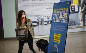 A passenger wearing a face mask as a precaution against the novel coronavirus walks past a sign at Heathrow airport, west London, on May 22, 2020.