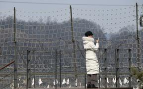 A visitor looks over a military fence on a viewing deck at Imjingak peace park, near the Demilitarised Zone (DMZ) dividing the two Koreas in Paju on 1 January 2020.