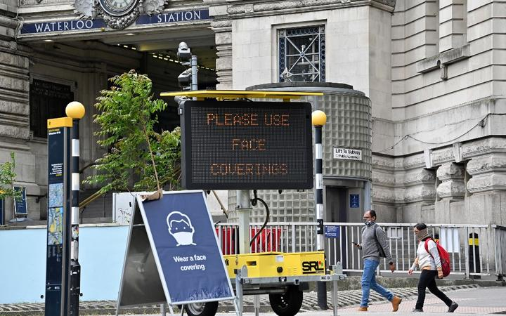 A sign tells passengers to 'wear a face covering' at Waterloo train station in central London , on June 8, 2020, as the UK government's planned 14-day quarantine for international arrivals to limit the spread of the novel coronavirus COVID-19 begins.