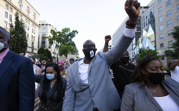 Philonise Floyd (centre), George Floyd's brother, holds up his fist as he marches with others near the White House, to protest police brutality and racism
