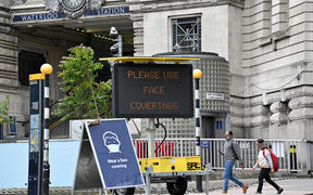 A sign tells passengers to 'wear a face covering' at Waterloo train station in central London during the Covid-19 pandemic