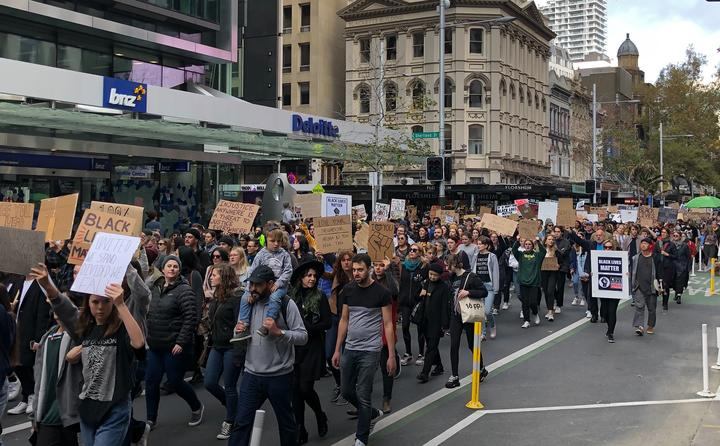 The Black Lives Matter protesters make their way down Queen Street in Auckland.