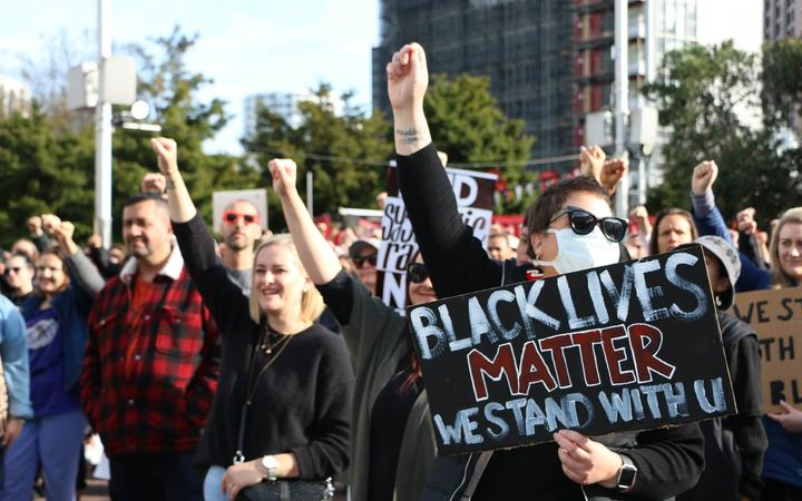 Protesters raise their fists to show solidarity at the Black Lives Matter march in Auckland on 14 June, 2020.