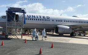 United Airlines workers in Majuro wore full-body PPE before going onto a United flight in May