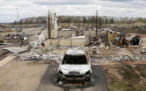A charred vehicle and home are pictured in the Beacon Hill neighbourhood of Fort McMurray.