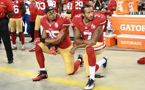 Colin Kaepernick #7 and Eric Reid #35 of the San Francisco 49ers kneel in protest during the national anthem prior to playing the Los Angeles Rams in their NFL game 2016.