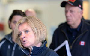 Alberta Premier Rachel Notley (left) speaks at the Fort McMurray fire department as fire chief Darby Allen looks on.
