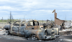 A burned out truck and the remains of a house in the Beacon Hill neighbourhood of Fort McMurray.