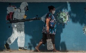 A woman walks past graffiti in Rio de Janeiro depicting a man performing a disinfection and the face of President Jair Bolsonaro represented by a virus.