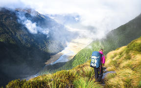 A hiker walks along a trail in the Matukituki Valley in Mt Aspiring National Park.