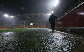 A  security guard walks off a flooded Suncorp Stadium  following the postponement of the ANZAC Test to Sunday 3rd May, Brisbane ,Australia on May 1, 2015.