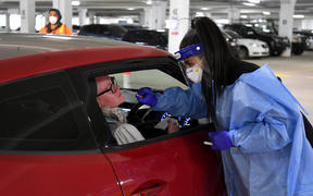 Medical staff perform a Covid-19 test at a drive-through testing site in a Melbourne carpark on 1 May.