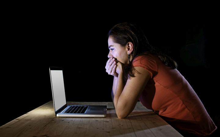 young and depressed worker or student woman working with computer laptop alone late at night in stress suffering internet bullying victim of social network