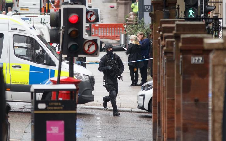 An armed specialist police officer runs as he responds at the scene of a fatal stabbing incident at the Park Inn Hotel in central Glasgow on June 26, 2020.