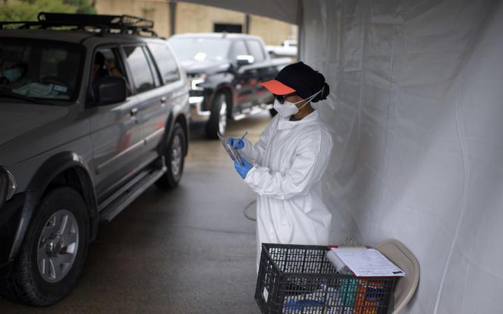 A healthcare worker takes information as cars line up at a Covid-19 testing site in Houston, Texas, 25 June 2020.