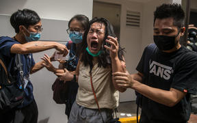 A woman reacts after she was hit with pepper spray deployed by police as they cleared a street where protesters were rallying against a new national security law in Hong Kong on July 1, 2020.