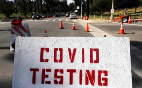 People in cars (TOP L) are lined up to be tested for COVID-19 as they make their way to a parking lot at Dodger Stadium amid the coronavirus pandemic on June 26, 2020 in Los Angeles, California.