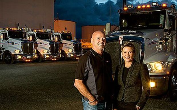 Couple stand in front of big trucks