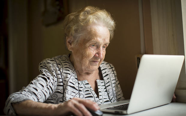 An elderly woman works on a laptop