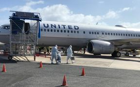 For the one flight per month now scheduled to the Marshall Islands, United Airlines Majuro workers don full-body personal protective gear to briefly enter the plane.