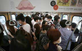 An inside of train is packed with passengers on a JR Line  during a rush hour in Ota Ward, Tokyo  on June 15, 2020,