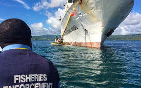 A Papua New Guinea fisheries officer prepares to board a fishing vessel for inspection in Rabaul.