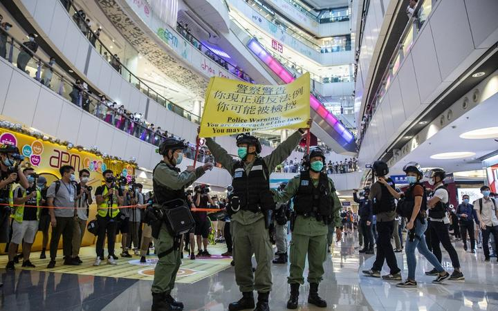 Riot police hold up a warning flag during a demonstration in a mall in Hong Kong on July 6, 2020, in response to a new national security law.
