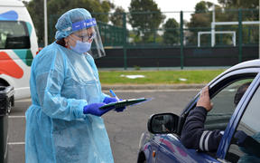 Health officials check people at a Covid-19 testing centre in Melbourne
