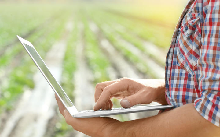 Male farmer with laptop in field, closeup