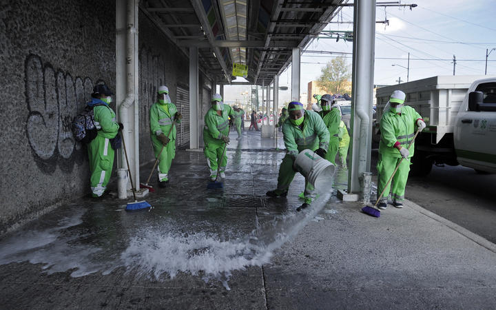 Municipal workers clean and disinfect a sidewalk in Tepito neighborhood in Mexico City