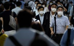 People wearing face masks walk during the evening rush hour from Shinagawa railway station in Tokyo on June 24, 2020.