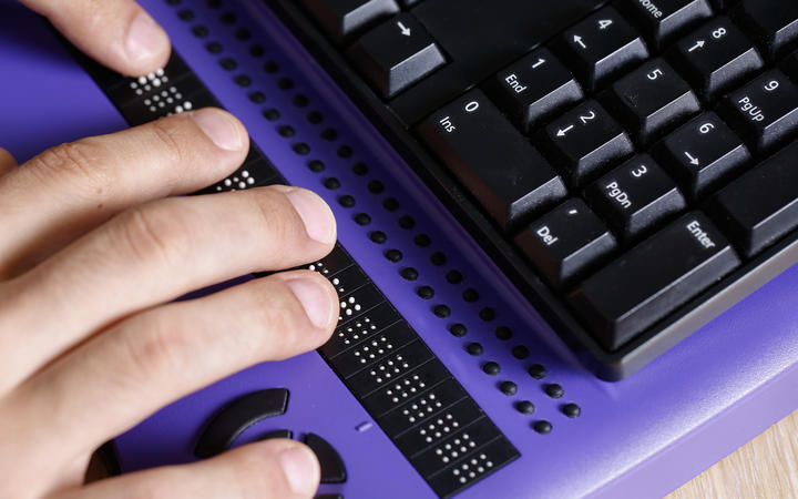 Blind person using computer with braille keyboard. Visual impairment, independent life concept.