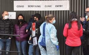A medical worker (C) speaks to people queueing outside a COVID-19 coronavirus testing venue at The Royal Melbourne Hospital in Melbourne on July 16, 2020.