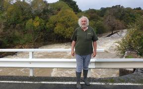 Mike Butler on a bridge above the raging Waiharakeke Stream