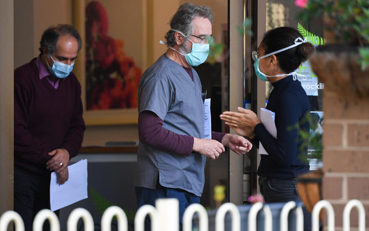 People wearing face masks are seen at the entrance of the Menarock Life aged care facility, where a cluster of infections has been reported.  There are Covid-19 cases linked to 40 aged care facilities in Victoria.