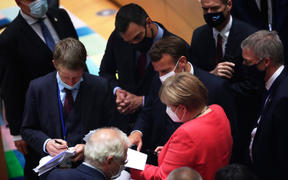 German Chancellor Angela Merkel speaks with Spain's Prime Minister Pedro Sanchez (centre) and French President Emmanuel Macron during a round table meeting at an EU summit over a post-virus economic rescue plan in Brussels, on July 20, 2020.