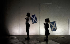 Two young girls holding saltires, watch the entertainment outside the Scottish Parliament in Edinburgh on September 18, 2014, during Scotland's independence referendum.
