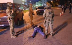 The suspect in the hostage situation lies on the ground after being detained by law enforcement officers in the city of Lutsk, Ukraine, on July 21, 2020.
