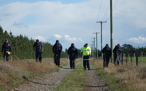 Police investigators canvass Main Rakaia Road, where the woman's body was found.