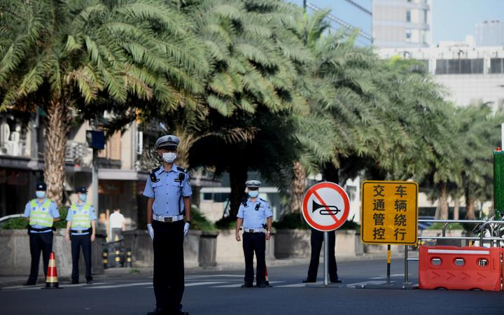 Policemen stand guard on a road leading to the US Consulate in Chengdu.