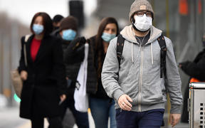 Commuters walk past Melbourne's Flinders Street Station on July 23, 2020 on the first day of the mandatory wearing of face masks in public areas as the city experiences an outbreak of the COVID-19 coronavirus.